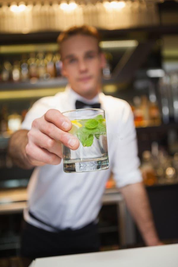 Cocktail de oferecimento do barman feliz à câmera imagens de stock royalty free