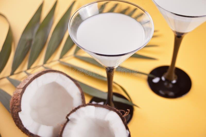 Cocktail de Pina Colada sur la table jaune avec la palmette et la noix de coco sur le fond photographie stock