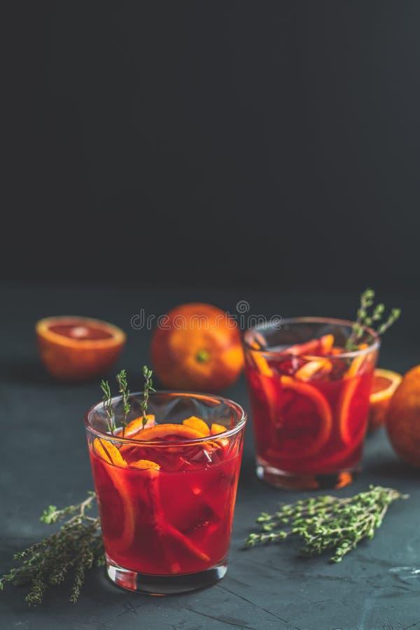 Cocktail de scintillement de vodka d'orange sanguine sur le fond concret noir photographie stock libre de droits