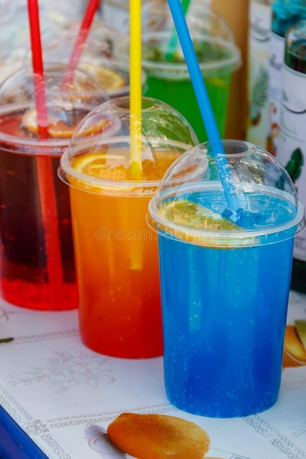 Cocktail de tonificação frios coloridos em uns copos plásticos com palhas do cocktail imagens de stock