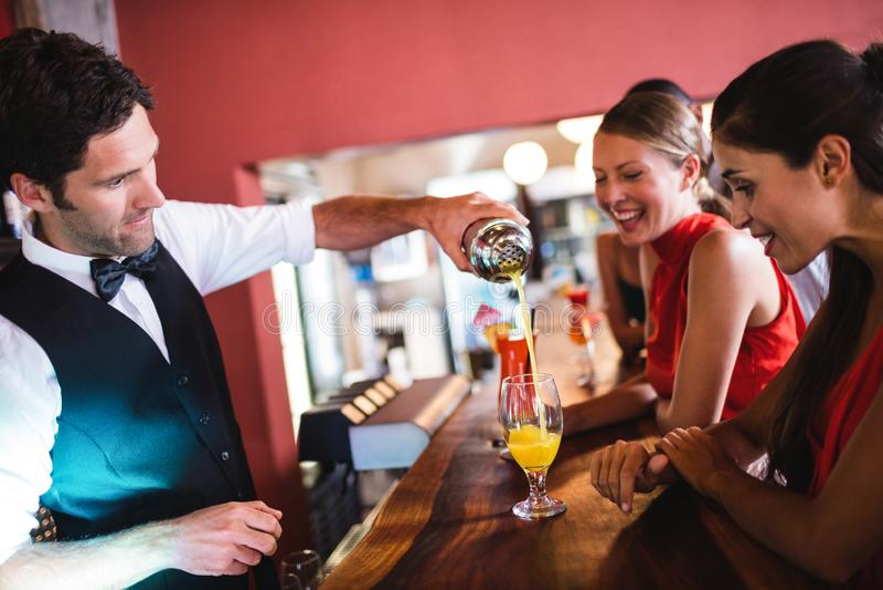 Cocktail de versement de barman en verre au compteur de barre photo libre de droits