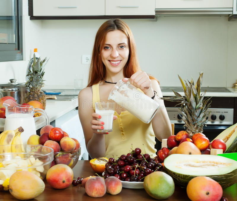 Cocktail de versement de lait de femme heureuse avec des fruits photographie stock
