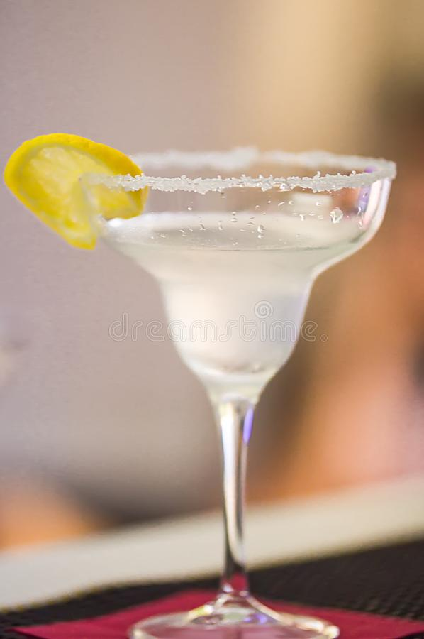 Cocktail dell'alcool della margarita in un vetro su un fondo delle luci intense i con il limone immagine stock libera da diritti