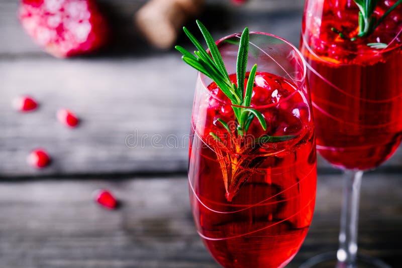Cocktail della mimosa del champagne del melograno con i rosmarini immagini stock libere da diritti