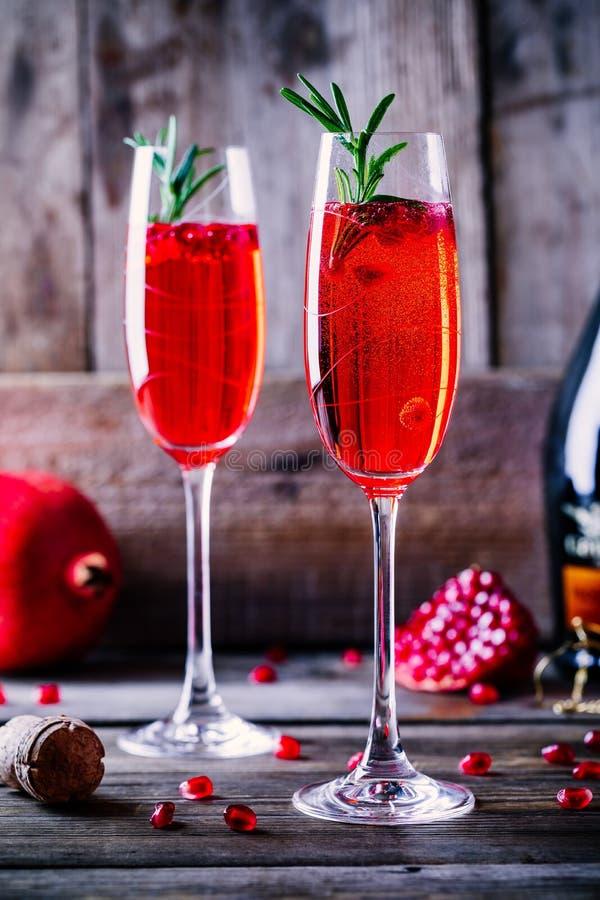 Cocktail della mimosa del champagne del melograno con i rosmarini fotografie stock
