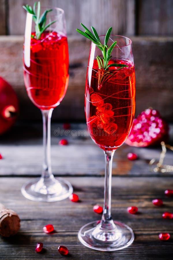 Cocktail della mimosa del champagne del melograno con i rosmarini immagine stock