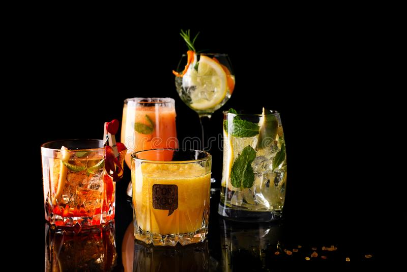 cocktail della Whiskey-cola, mojito-cocktail, cocktail arancio, cocktail della fragola in vetri di vetro con le paglie fotografie stock libere da diritti