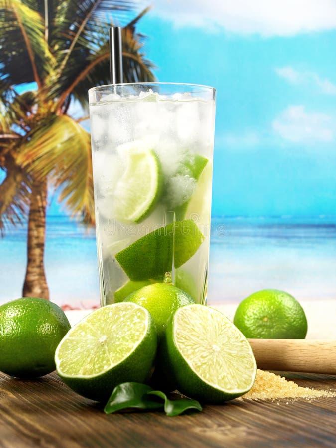 Cocktail di Caipirinha con le calce alla spiaggia fotografia stock