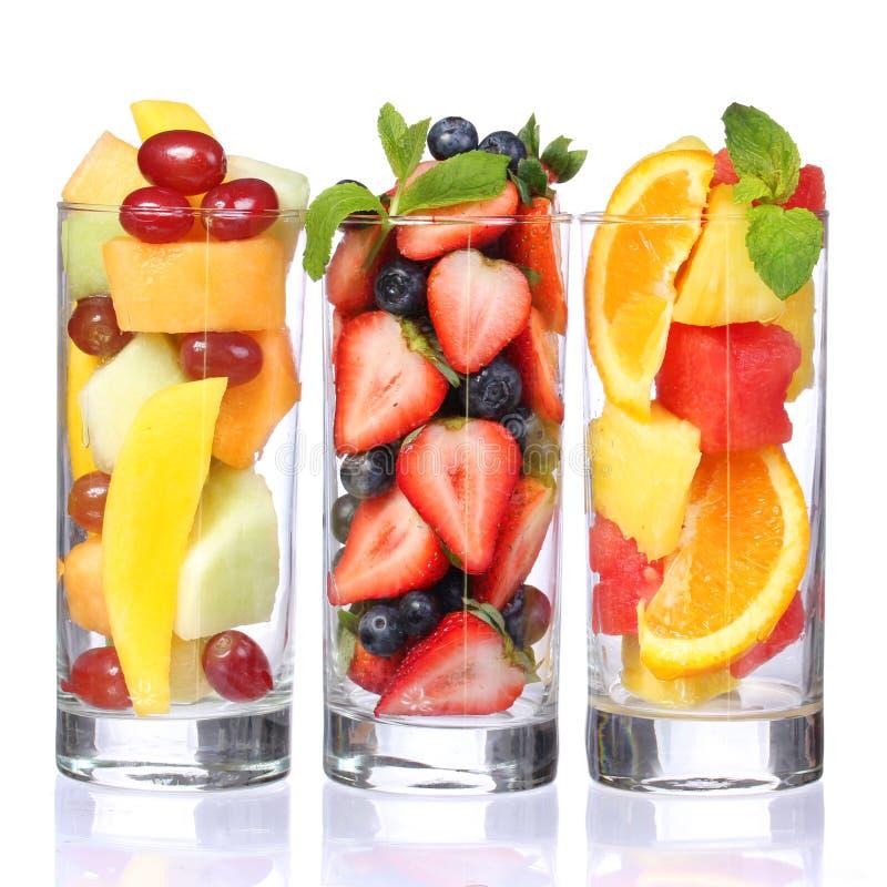 Cocktail di frutta isolati su bianco. Pezzi freschi di frutta in vetri con la menta sulla cima. fotografia stock