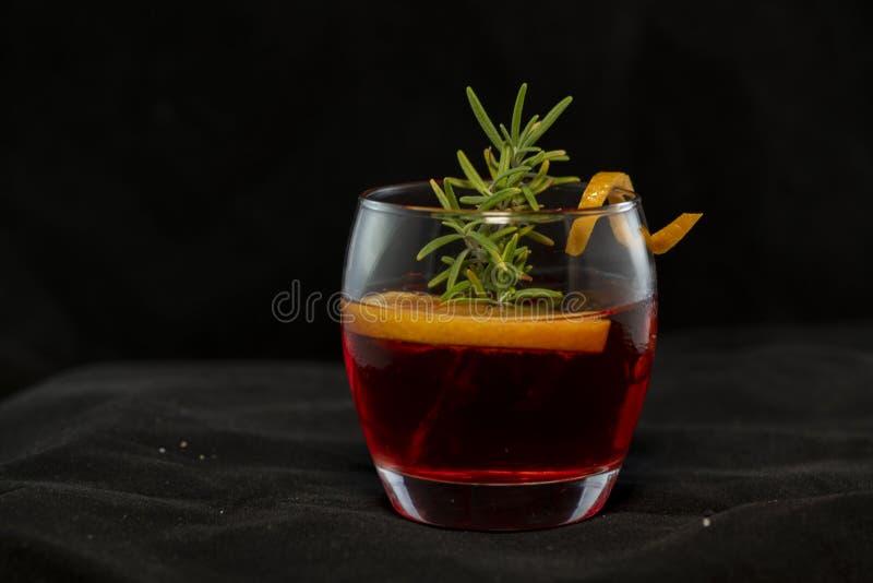 Cocktail di Gotfather con il whiskey di bourbon, l'amaretto, il cuneo arancio ed i rosmarini fotografia stock libera da diritti