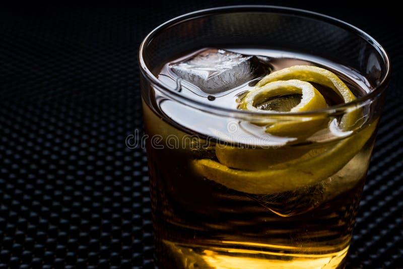 Cocktail di Highball con la buccia ed il ghiaccio di limone immagini stock libere da diritti
