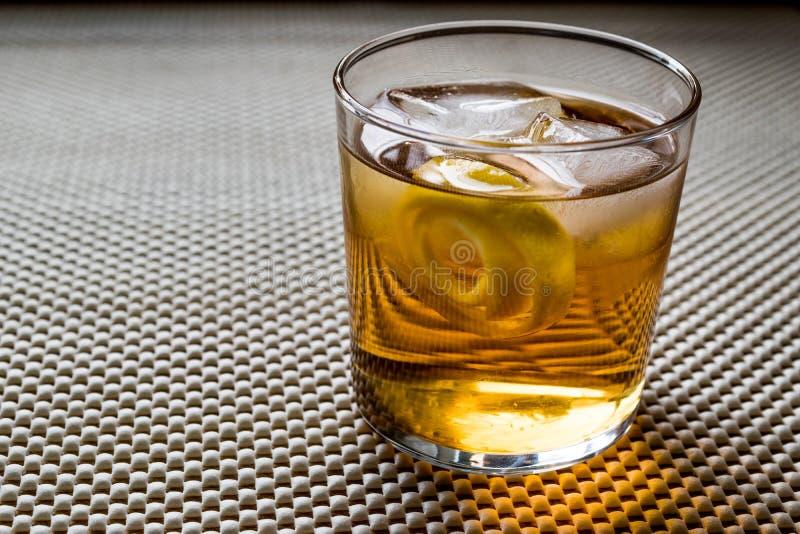 Cocktail di Highball con la buccia ed il ghiaccio di limone immagine stock