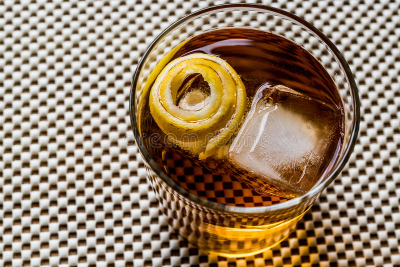Cocktail di Highball con la buccia ed il ghiaccio di limone fotografia stock libera da diritti