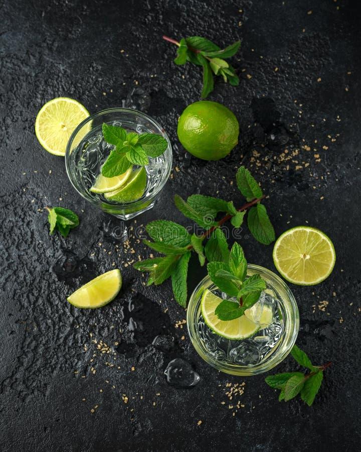 Cocktail di Mojito con rum, calce e la menta in vetro Bevanda fredda di estate con ghiaccio immagini stock