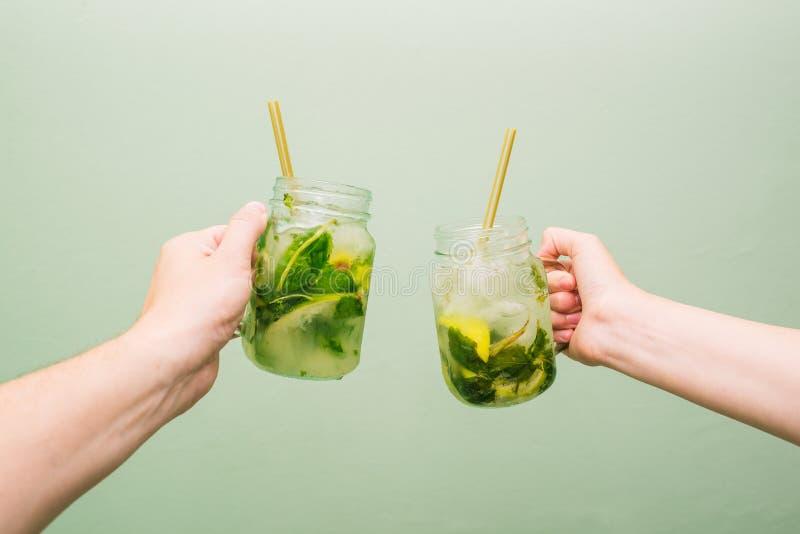 Cocktail di Mojito in una coppa di vetro La gente tiene nei loro gamberi una bevanda fredda dell'estate con calce, la menta ed il fotografie stock libere da diritti