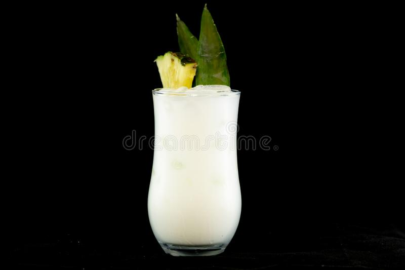 Cocktail di Pina Colada con il succo di ananas, il rum bianco e la crema della noce di cocco decorati con la frutta e la foglia d fotografie stock