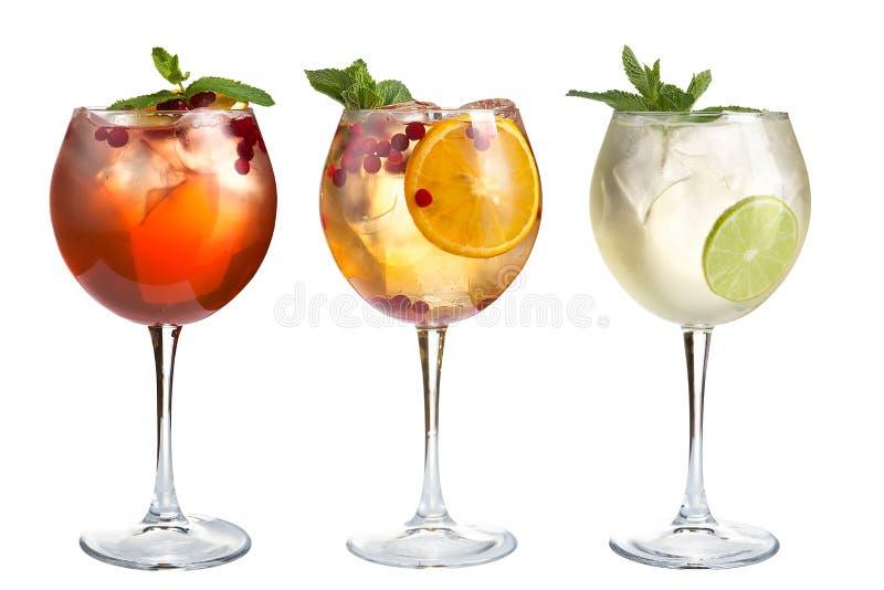 Cocktail di rinfresco con la menta, i frutti e le bacche su un fondo bianco Metta di tre cocktail in calici di vetro fotografie stock libere da diritti