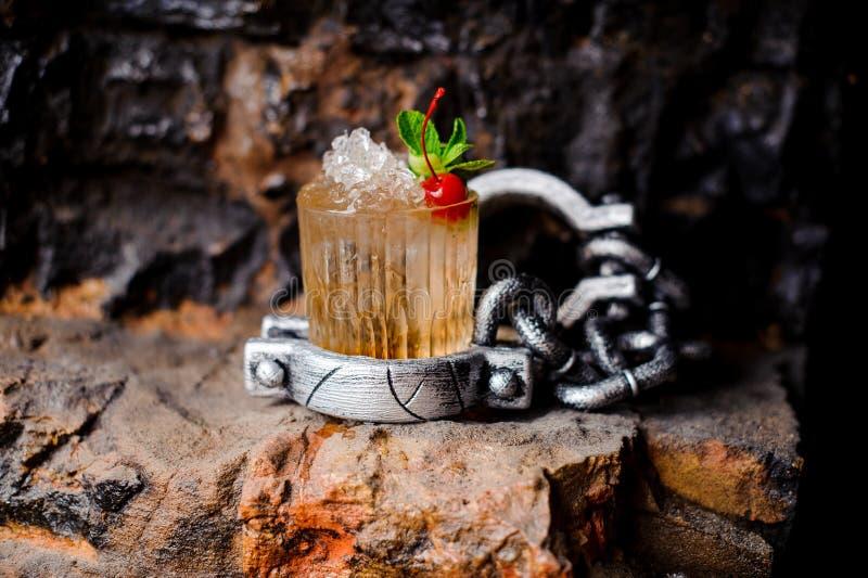 Cocktail do álcool com gelo esmagado, a cereja vermelha e a hortelã imagem de stock