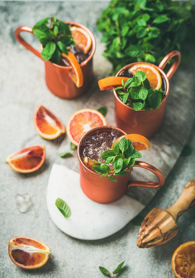 Cocktail do álcool da mula de Moscou da laranja pigmentada sobre o fundo concreto fotografia de stock