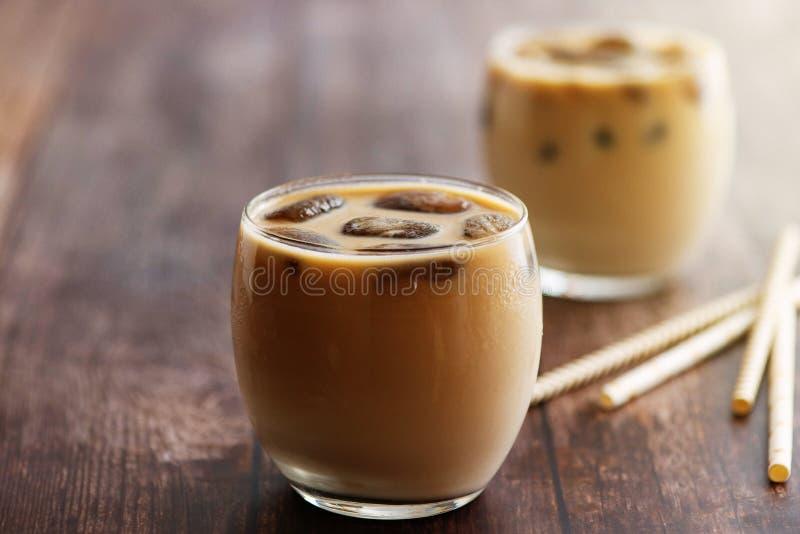 Cocktail do café do leite nos vidros com os cubos congelados do café na tabela de madeira Vista lateral imagem de stock