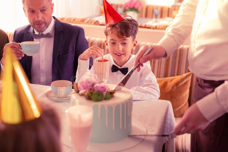 Cocktail do leite bebendo do menino do aniversário e bolo de espera fotos de stock