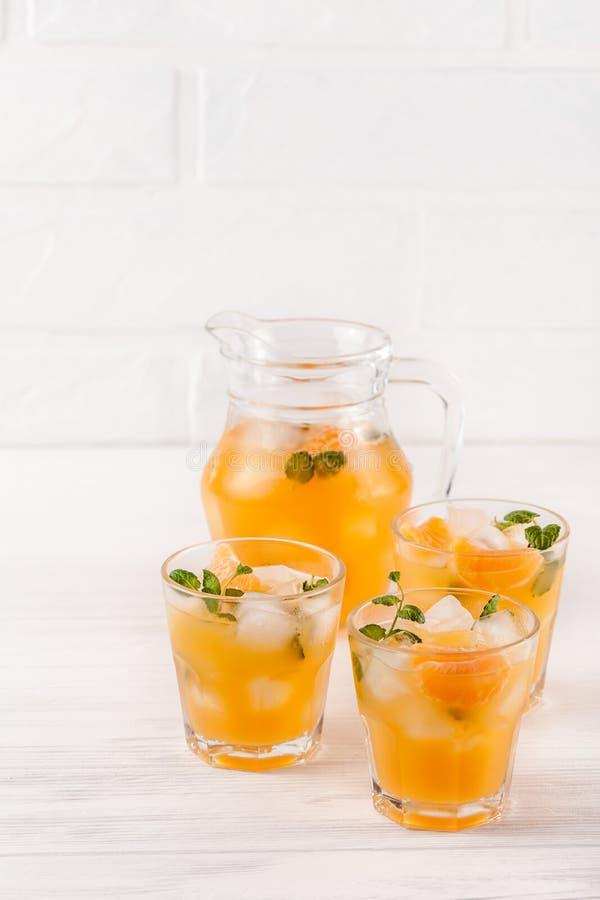 Cocktail do mandarino com gelo e hortelã nos vidros e no jarro bonitos, citrino maduro fresco no fundo de madeira branco Suco de  imagem de stock