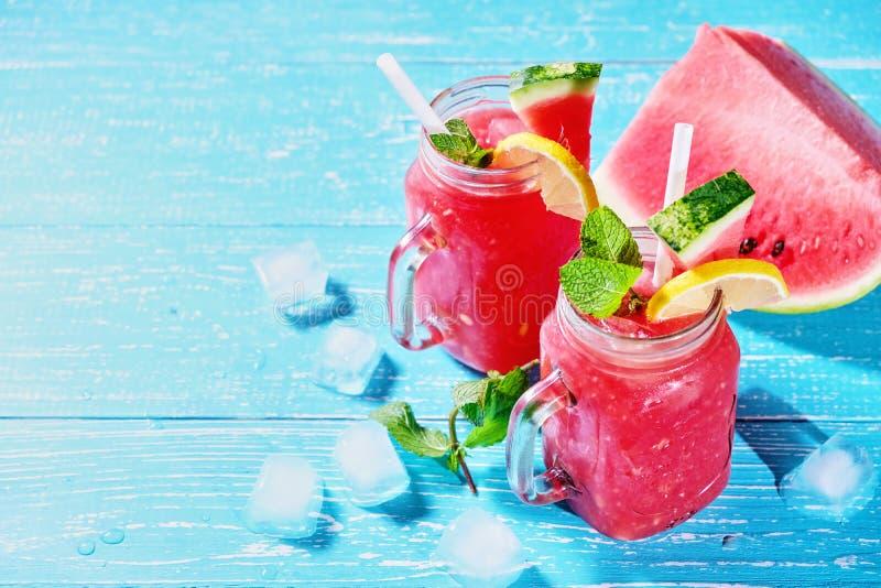 Cocktail do verão da melancia com as folhas do gelo e de hortelã Bebida fria do rafrescamento no fundo de madeira azul com espaço imagem de stock royalty free