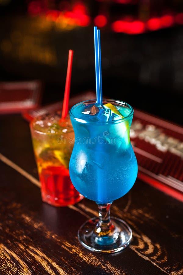 Cocktail dois diferente na barra Lagoa azul colorida e cocktail alaranjado imagens de stock royalty free