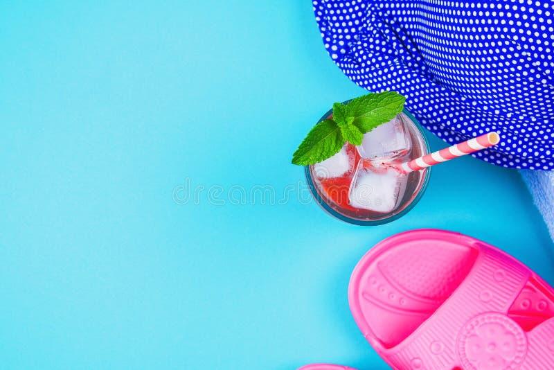 Cocktail dos flip-flops, do roupa de banho, da toalha e do gelo em um fundo pastel azul Resto, curso Vista superior Copie o espaç fotografia de stock