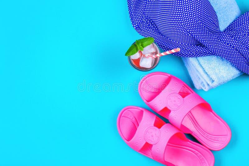 Cocktail dos flip-flops, do roupa de banho, da toalha e do gelo em um fundo pastel azul Resto, curso Vista superior Copie o espaç fotografia de stock royalty free