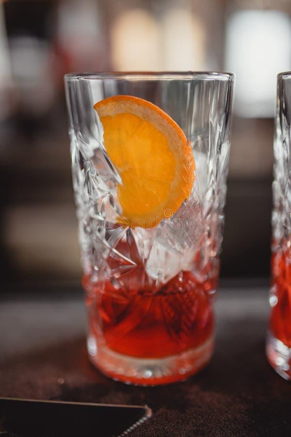 Cocktail em uma barra do cocktail com alaranjado e o vermelho imagens de stock