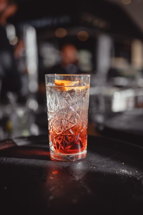Cocktail em uma barra do cocktail com alaranjado e o vermelho foto de stock