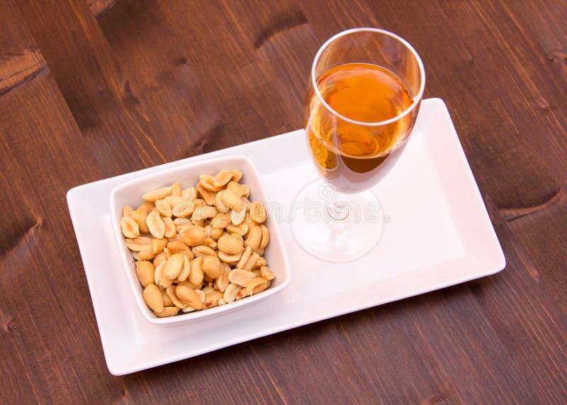 Cocktail en gezouten noten op hout van hierboven stock afbeelding