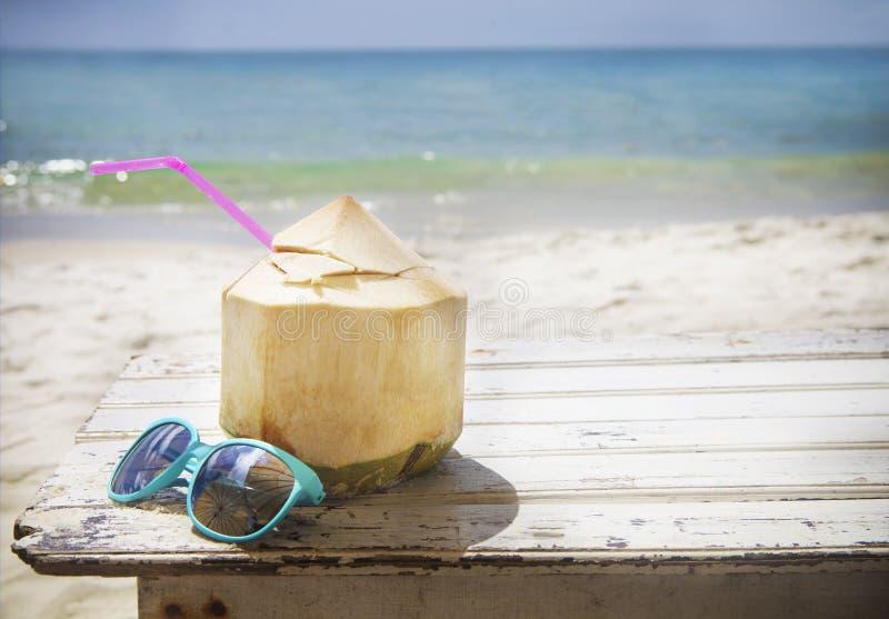 Cocktail et lunettes de soleil frais de noix de coco sur la plage tropicale image stock