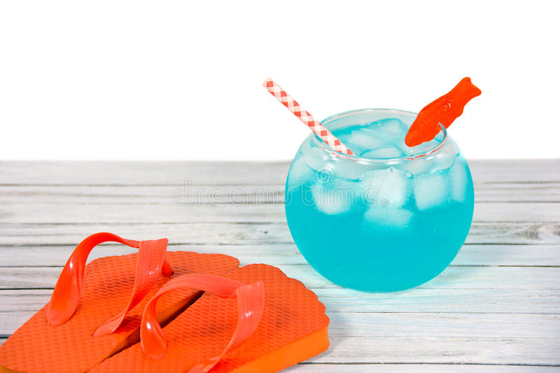 Cocktail in fish bowl with flip-flops royalty free stock photo