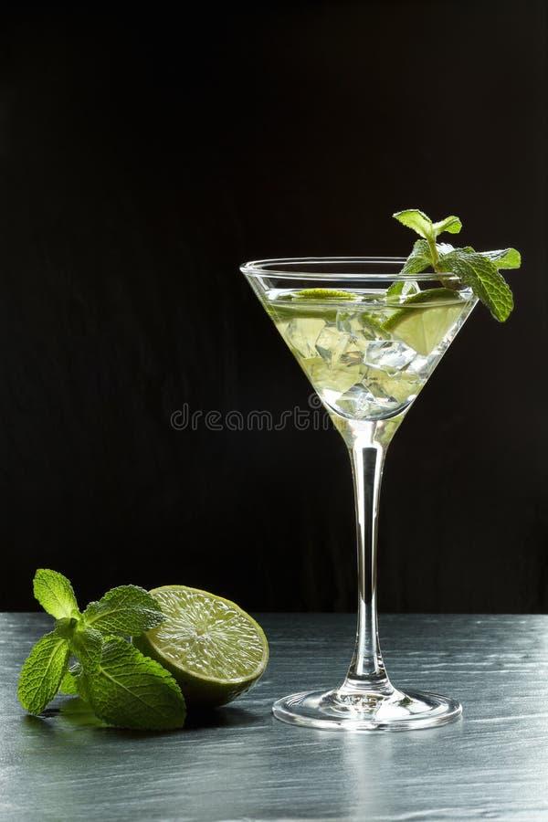 Cocktail frais d'été avec les tranches de chaux, la glace écrasée et les feuilles en bon état dans un de verre de martini éclairé images libres de droits