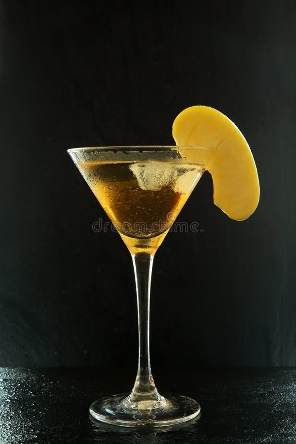 Cocktail frais d'appletini d'été dans un verre de martini avec une tranche de pomme sur une surface texturisée noire avec des bai photos stock