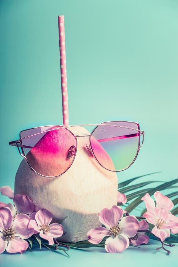 Cocktail frais de noix de coco avec la paille rose de boissons, les palmettes en verre de soleil et les fleurs tropicales au fond images stock