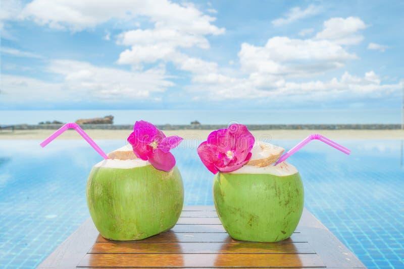 Cocktail frais tropical de noix de coco avec la piscine et plage dans l'océan, Phuket, Thaïlande photographie stock libre de droits