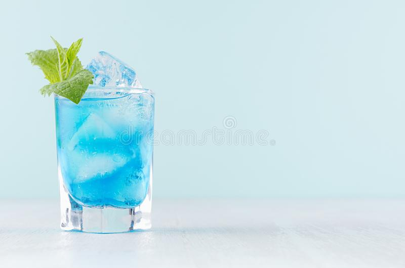 Cocktail freddo esotico di vetro di colpo con il curacao blu, i cubetti di ghiaccio, la menta verde sul fondo di colore della men fotografie stock libere da diritti