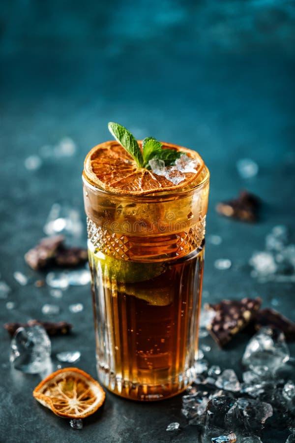Cocktail fresco com cola, cal, chocolate e gelo no vidro em escuro - fundo azul Bebida e cocktail frios do verão imagens de stock