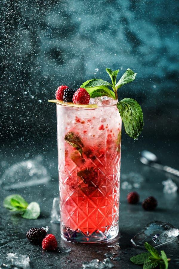 Cocktail fresco delle bacche con il lampone, la mora, la menta ed il ghiaccio in vetro del barattolo su fondo blu scuro fotografie stock libere da diritti