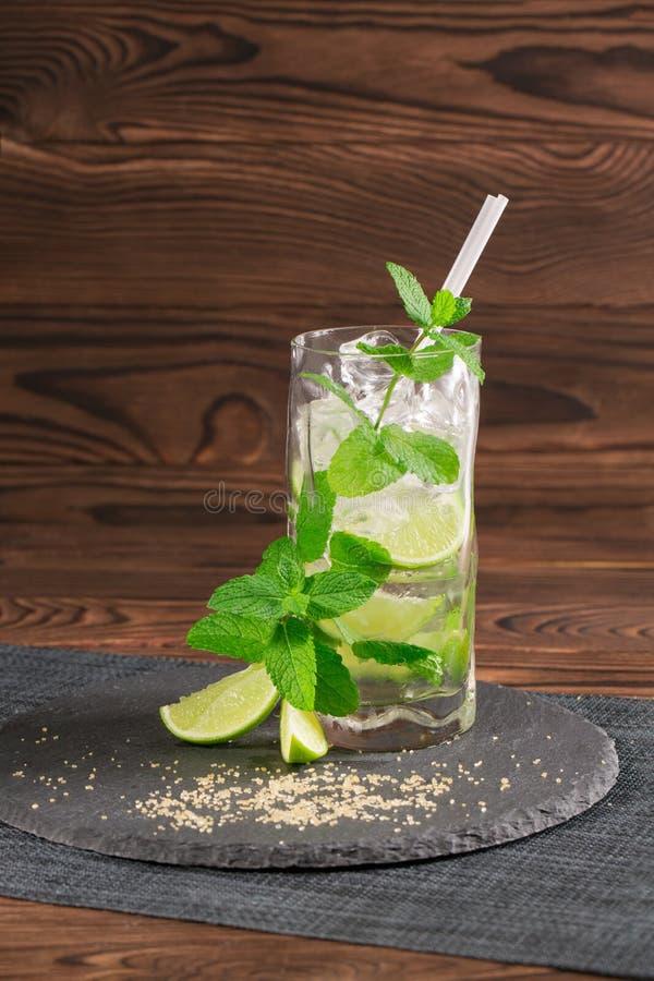 Cocktail fresco di mojito con rum, la menta, i cubetti di ghiaccio e la calce in un vetro di highball sui precedenti di legno Bev fotografia stock