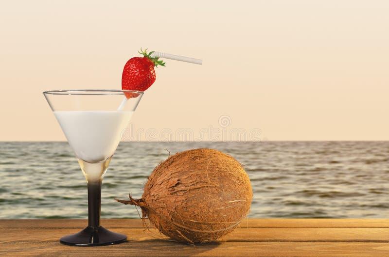 Cocktail fresco do coco em uma praia tropical durante o por do sol foto de stock