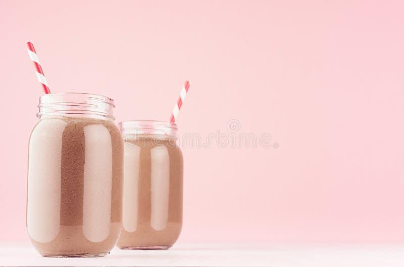 Cocktail fresco freddo del latte di estate di cacao in barattoli con paglia sul bordo di legno bianco e sulla parete rosa pastell fotografia stock