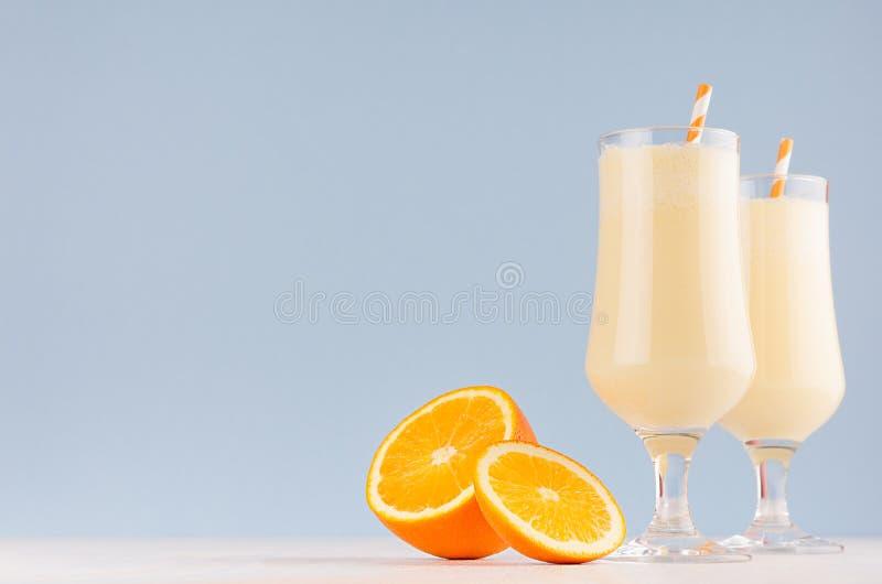Cocktail fresco freddo del latte di estate dell'arancia con i pezzi succosi frutta, paglia sul bordo di legno bianco e parete blu immagine stock libera da diritti