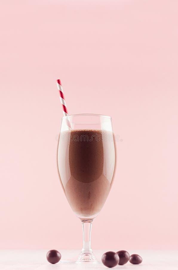 Cocktail fresco frio do leite do verão do cacau com doces de chocolate, palha na placa de madeira branca e a parede cor-de-rosa p fotos de stock royalty free