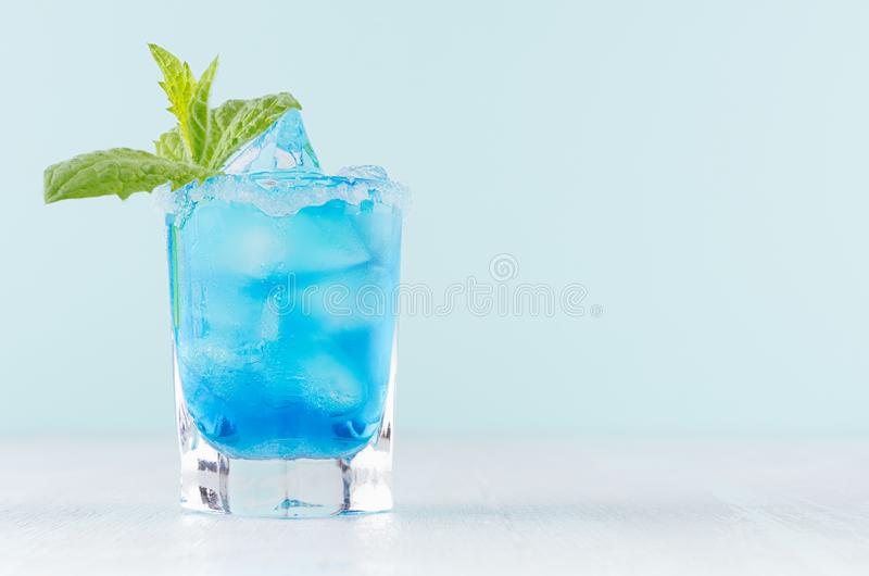 Cocktail fresco tropical com licor azul de Curaçau, cubo de gelo, borda do açúcar, hortelã verde no vidro disparado congelado no  fotografia de stock royalty free