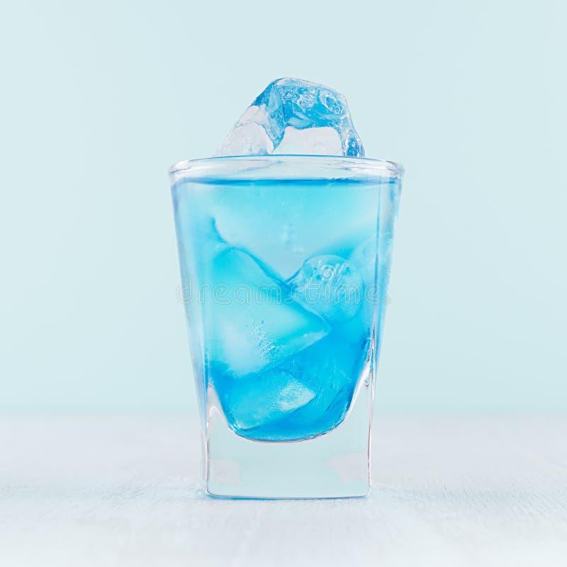 Cocktail fresco tropicale dell'alcool con il liquore blu del curacao, cubetto di ghiaccio in vetro sparato congelato su bianco de fotografia stock