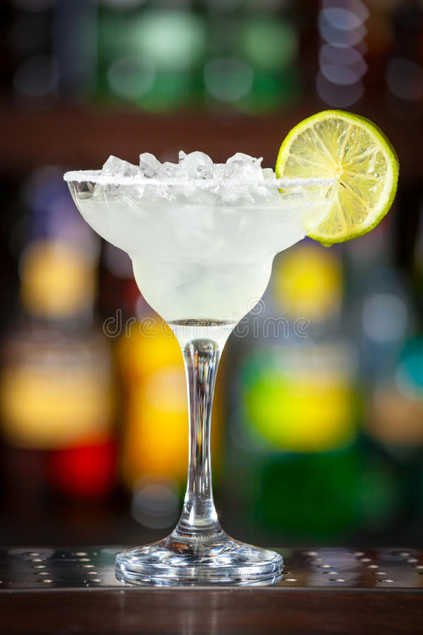 Cocktail garnished with lime. Cocktail garnished with lime standing on the bar counter stock photography